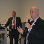 DAI Board member Chris Roberts presenting at ADI2015 and Marc Wortmann, CE of ADI in the background